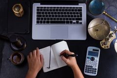 Workspace hero header with law gavel. Legal book and laptop keyboard, open empty notebook with someones hands writting in notebook, top view flat lay scene Royalty Free Stock Photos