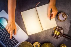 Workspace hero header with law gavel. Legal book and laptop keyboard, hands typing and writting in notebook, top view flat lay scene, retro toned Royalty Free Stock Photography