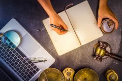 Workspace hero header with law gavel. Legal book and laptop keyboard, hands writting in notebook, top view flat lay scene, retro toned Royalty Free Stock Photo