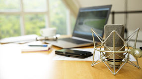 Workspace for journalism with condenser microphone, laptop, cell. Phone and notepad on a desktop at the window, short panoramic banner for website headerwith Royalty Free Stock Photography