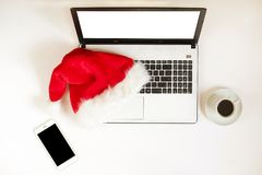 Workspace with laptop and christmas gift and santa hat on white background flat lay, top view, copy space. Business christmas holidays concept, holiday online Royalty Free Stock Images