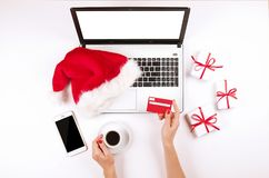 Workspace with laptop and christmas gift and santa hat on white background flat lay, top view, copy space. Stock Photos