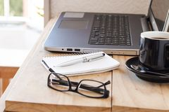Workspace with a laptop, coffee, notebook, and a glasses. Business workspace with a laptop, coffee, notebook, and a glasses Royalty Free Stock Photo