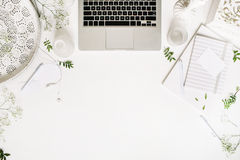 Workspace with laptop, headphones, pen, notebook, sketchbook, white vintage tray, candlesticks on white background Stock Image