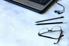 Workspace, many different items including a laptop, glasses, notebook, and headphones are on the table stock images