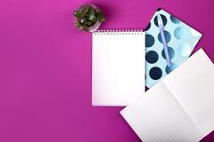Workspace med anteckningsbokpappersmellanrumet, blommor, penna Arkivfoto