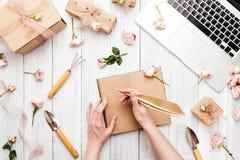 Workspace med ett bärbar datortangentbord, steg blommor, gåvaaskar fotografering för bildbyråer
