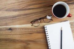 Workspace med kaffekoppen, ögonblickliga foto, anmärkningspapper och notebo Arkivfoto