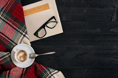 Workspace med tidningen, kaffekopp, halsduk, exponeringsglas Stilfullt kontorsskrivbord Höst- eller vinterbegrepp Lekmanna- lägen royaltyfri fotografi