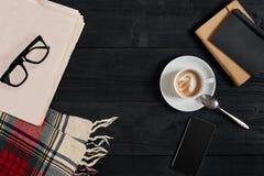 Workspace med tidningen, kaffekopp, halsduk, exponeringsglas Stilfullt kontorsskrivbord Höst- eller vinterbegrepp Lekmanna- lägen arkivbild
