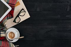 Workspace with newspaper, coffee cup, scarf, glasses. Stylish office desk. Autumn or Winter concept. Flat lay, top view. Workspace with newspaper, coffee cup Stock Images