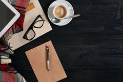 Workspace with newspaper, coffee cup, scarf, glasses. Stylish office desk. Autumn or Winter concept. Flat lay, top view Royalty Free Stock Photo