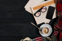 Workspace with newspaper, coffee cup, scarf, glasses. Stylish office desk. Autumn or Winter concept. Flat lay, top view. Workspace with newspaper, coffee cup Royalty Free Stock Photos