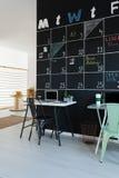Workspace next to blackboard. Simple trendy workspace next to blackboard calendar on wall Stock Images
