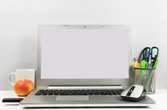 Workspace at the table with laptop, white screen, cup of coffee, apple, USB flash, and pencil box. stock photography