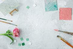 Workspace with palette knife, canvas painting, tulip flower and mosaic on gray backround stock photography