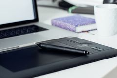 Workspace of professional retoucher. Laptop, stylus and tablet for retouching Stock Images