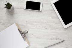 Workspace with smartphone, tablet, clipboard and pencil, overhead. Top view. Copy space stock image