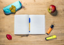 Workspace of the student with opened copybook, case, pen, apple, autumn maple leaf, markers on desk. Workspace of the student with opened copybook, case, pen stock photography