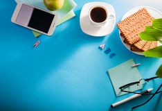 Workspace of a student. Studying with a cup of coffee and snacks, using a phone stock photo