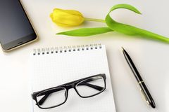 Workspace on table are tulip, notebook, glasses, smartphone and pen Stock Image