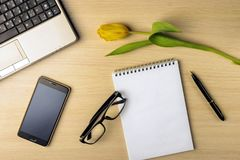 Workspace on the table are tulip, notebook, laptop, glasses, smartphone and pen Royalty Free Stock Images