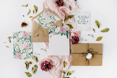 Workspace. Wedding invitation cards, craft envelopes, pink and red roses. And green leaves on white background. Overhead view. Flat lay, top view Royalty Free Stock Photography