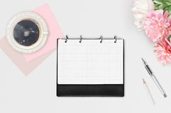 Workspace on white background. Three pink white peonies, cup of coffee, day planner, pen and white pencil. Flat lay. Business woma Royalty Free Stock Image