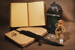 Workspace of the witch or sorcerer with old grimoires, charms an. Mystical still life with vintage books with strange paintings, old lantern, antique pen, wizard stock images