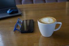 Workspace z laptopem, filiżanka kawy i myszą dla laptopu, telefon, szkła na białym drewnianym stole fotografia royalty free