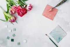 Workspace z paleta nożem, brezentowym obrazem, tulipanowym kwiatem i mozaiką na szarym backround, zdjęcia stock