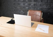 Business work place with chair, wooden table, touch pad, laptop computer and paper documents. stock photos