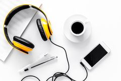 Worktable of composer today. Headphones, phone, music notes on white background top view Stock Photos