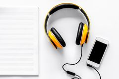 Worktable of composer today. Headphones, phone, music notes on white background top view Stock Image