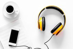 Worktable of composer today. Headphones, phone, music notes on white background top view Stock Images