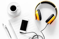 Worktable of composer today. Headphones, phone, music notes on white background top view Royalty Free Stock Photography