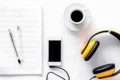 Worktable of composer today. Headphones, phone, music notes on white background top view Stock Photo