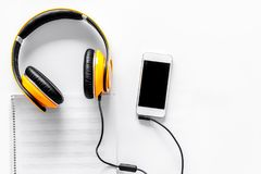 Worktable of composer today. Headphones, phone, music notes on white background top view copyspace Royalty Free Stock Images