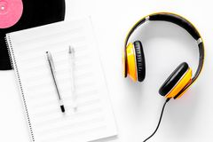 Worktable of composer today. Headphones, vinyl record, music notes on white background top view Stock Photos
