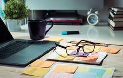 Worktable med datorbärbara datorn och notepaden, kaffekopp i morgon Arkivbild