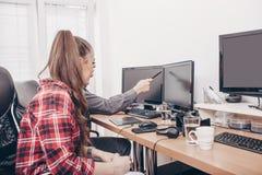 Workteam в офисе работая на настольном компьютере стоковое изображение