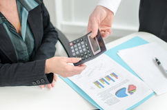 Workteam analyzing graphs and holding a calculator Stock Image