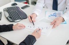 Workteam die aan een economisch document werken stock afbeelding