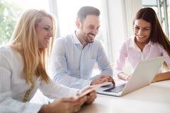 Workteam i regeringsställning som tillsammans arbetar på bärbara datorn Arkivfoton