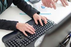 Workteam som arbetar på en dator Arkivfoto