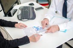 Workteam som arbetar på ett ekonomiskt dokument Fotografering för Bildbyråer