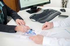 Workteam working on a economic document Stock Photo