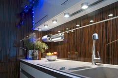 Worktop在棕色t的一个时兴的厨房里向水槽和搅拌器扔石头 免版税库存照片