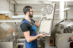 Workwe with cliche at the manufacturing. Worker standing with cliche for cutting boxes at the vintage printing manufacturing Royalty Free Stock Images