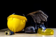 Workwear, helmet, gloves and glasses on a wooden working table. Stock Images